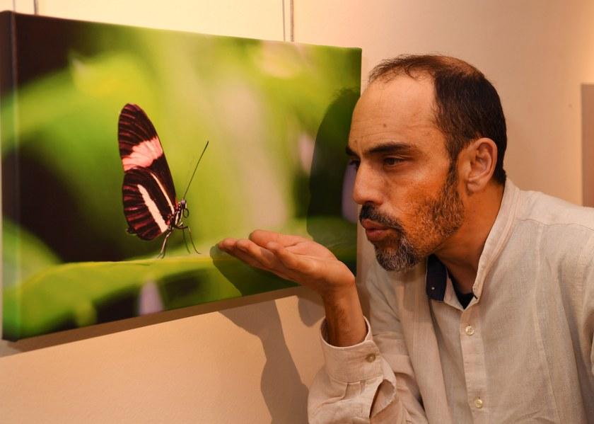 El fotógrafo junto a una de sus obras donde aparece una mariposa