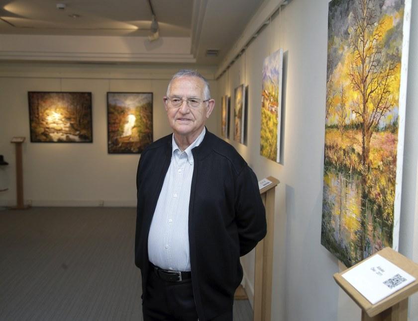 Mariano Herrero posando al lado de uno de sus cuadros